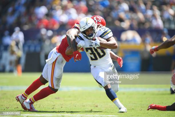 Running back Austin Ekeler of the Los Angeles Chargers is hit by linebacker Anthony Hitchens of the Kansas City Chiefs in the first quarter at...