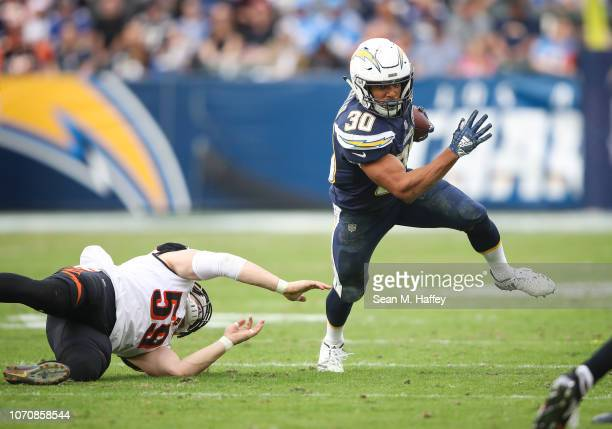 Running back Austin Ekeler of the Los Angeles Chargers makes a run play in front of outside linebacker Nick Vigil of the Cincinnati Bengals in the...