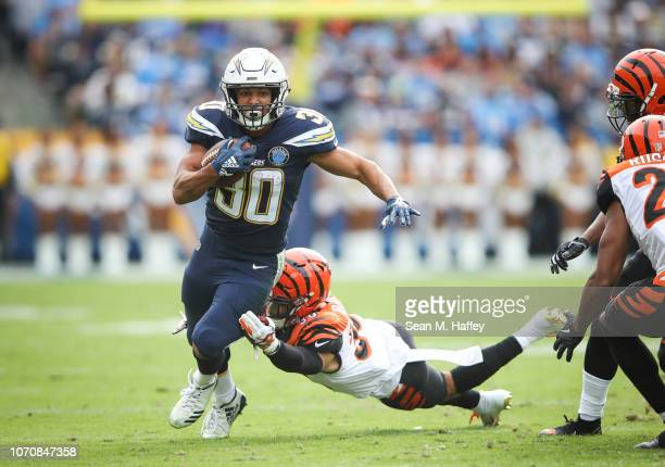 Running back Austin Ekeler of the Los Angeles Chargers makes a short run in the first quarter in front of free safety Jessie Bates of the Cincinnati...