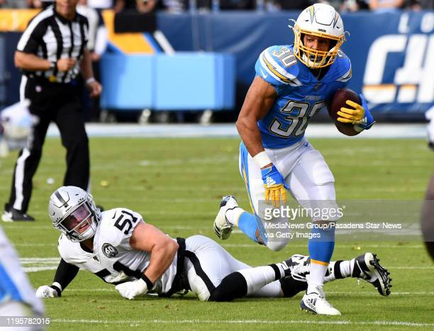 Running back Austin Ekeler of the Los Angeles Chargers runs for yardage past inside linebacker Will Compton of the Oakland Raiders in the first half...