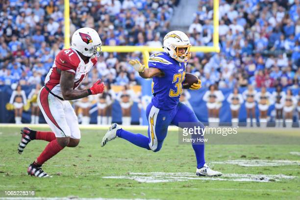Running back Austin Ekeler of the Los Angeles Chargers runs past free safety Antoine Bethea of the Arizona Cardinals in the third quarter at StubHub...