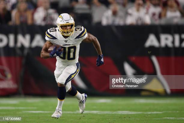 Running back Austin Ekeler of the Los Angeles Chargers rushes the football against the Arizona Cardinals during the NFL preseason game at State Farm...