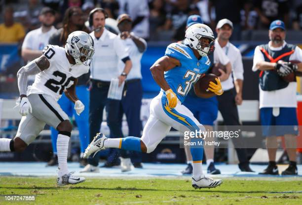 Running back Austin Ekeler of the Los Angeles Chargers scores a touchdown in the second quarter in front of defensive back Obi Melifonwu of the...