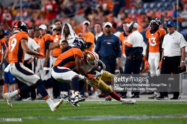 Running back Austin Walter of the San Francisco 49ers gets taken down by defensive back Rashard Causey of the Denver Broncos after making a big run...
