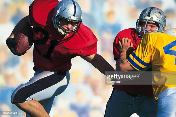 running back avoiding defender in football game - rush american football stock pictures, royalty-free photos & images