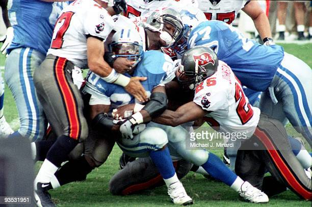 Running Back Barry Sanders of the Detroit Lions makes little yardage as he is tackled by Dirk Johnson of the Tampa Bay Buccaneers at Tampa Stadium on...