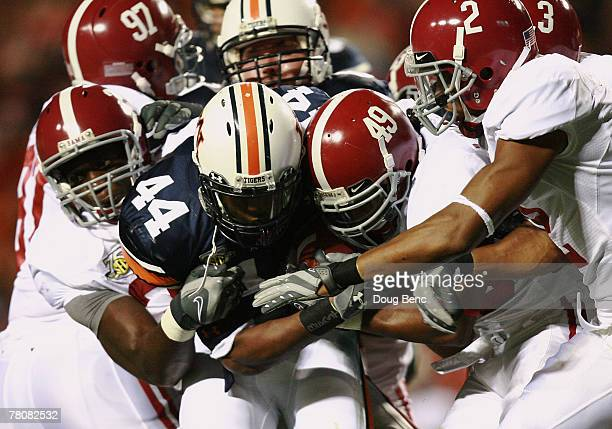 Running back Ben Tate of the Auburn Tigers drags a group of Alabama Crimson Tide defenders at JordanHare Stadium on November 24 2007 in Auburn Alabama