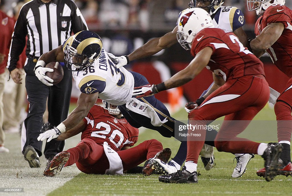 Running back Benny Cunningham #36 of the St Louis Rams dives for a first down as Antoine Cason #20 and Rashad Johnson #26 of the Arizona Cardinals defend during the fourth quarter of their NFL football game at University of Phoenix Stadium on December 8, 2013 in Glendale, Arizona.