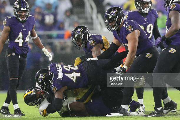 Running back Benny Snell of the Pittsburgh Steelers is tackled by inside linebacker Patrick Onwuasor of the Baltimore Ravens and other defenders...