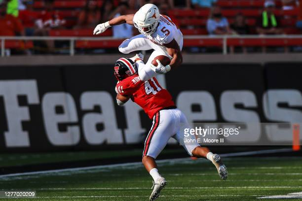 Running back Bijan Robinson of the Texas Longhorns is upended by linebacker Jacob Morgenstern of the Texas Tech Red Raiders during the second half of...