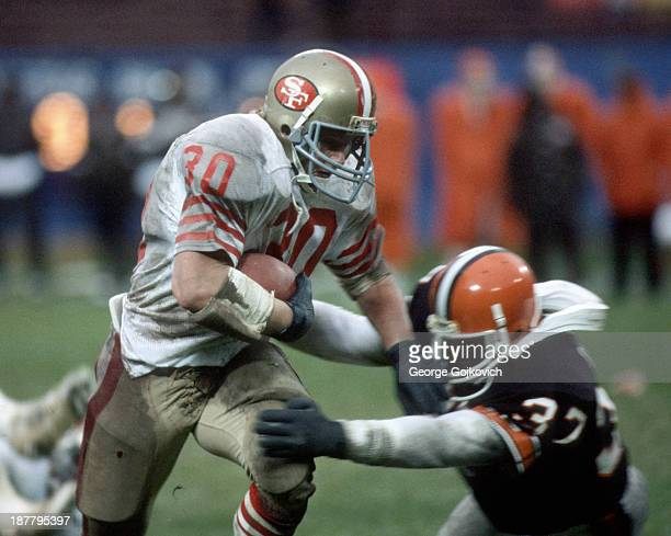 Running back Bill Ring of the San Francisco 49ers rushes against defensive back Chris Rockins of the Cleveland Browns at Municipal Stadium on...