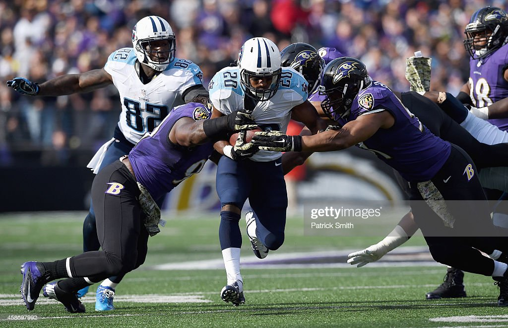 Running back Bishop Sankey #20 of the Tennessee Titans rushes againt defensive end Chris Canty #99 and outside linebacker Courtney Upshaw #91 of the Baltimore Ravens in the first half of a game at M&T Bank Stadium on November 9, 2014 in Baltimore, Maryland.