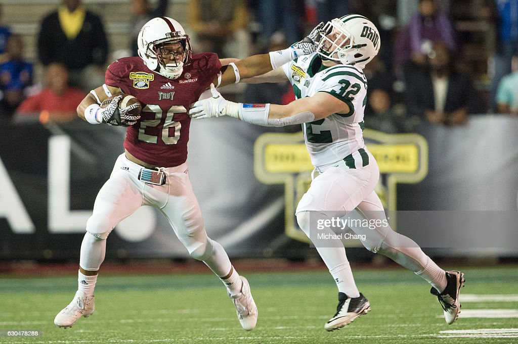 Running back B.J. Smith #26 of the Troy Trojans stiff arms linebacker Quentin Poling #32 of the Ohio Bobcats on December 23, 2016 in Mobile, Alabama.