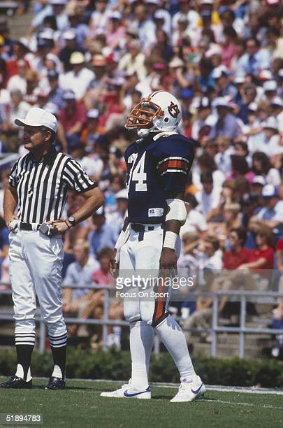 Running back Bo Jackson of the Auburn Tigers stands on the field next to a referee during a game in the 1980's