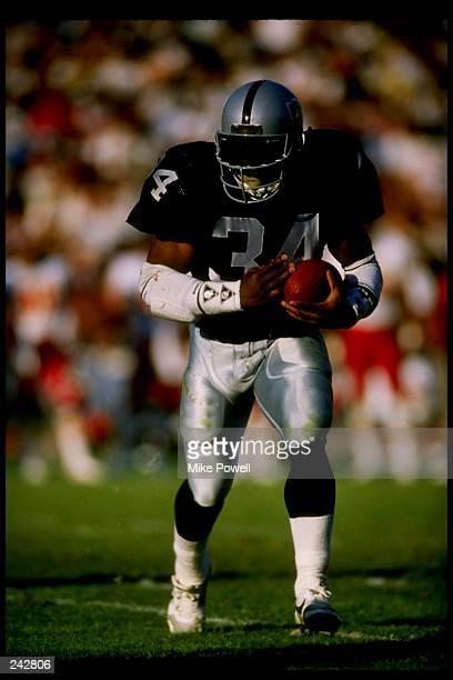 Running back Bo Jackson of the Los Angeles Raiders runs with the ball during a game versus the Kansas City Chiefs at the Los Angeles Memorial Colisem...