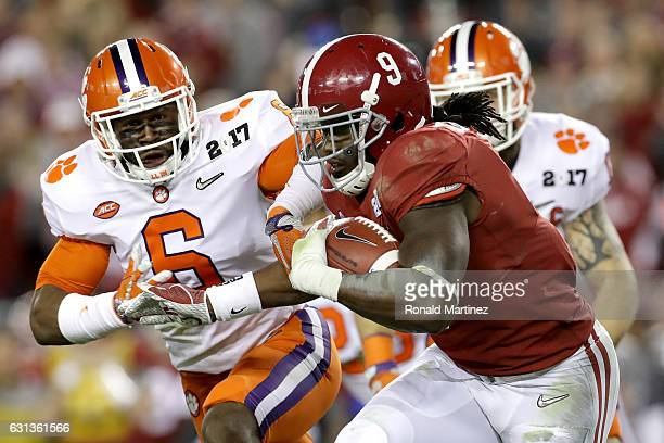 Running back Bo Scarbrough of the Alabama Crimson Tide carries the ball against linebacker Dorian O'Daniel of the Clemson Tigers during the first...