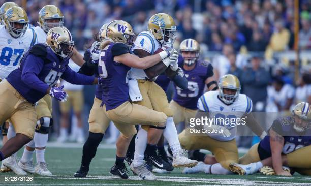 Running back Bolu Olorunfunmi of the UCLA Bruins is tackled by linebacker Ben BurrKirven of the Washington Huskies at Husky Stadium on October 28...