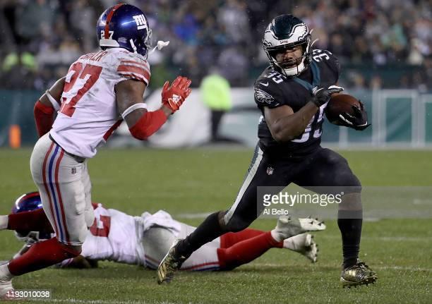 Running back Boston Scott of the Philadelphia Eagles carries the ball against the defense of cornerback Deandre Baker of the New York Giants during...