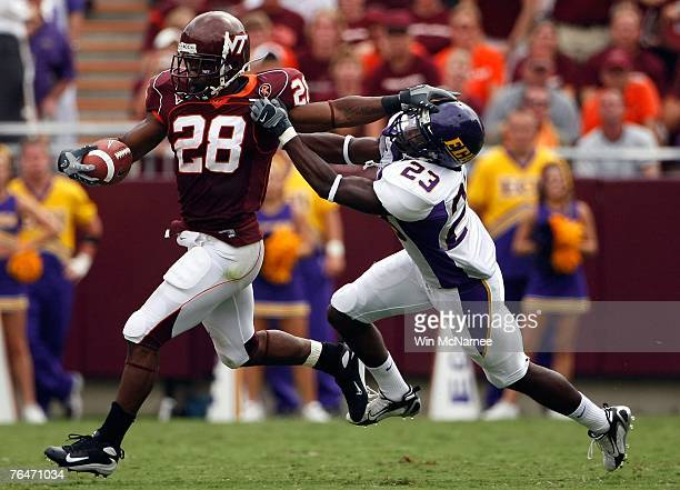 Running back Branden Ore of the Virginia Tech Hokies stiff arms defensive back Dekota Marshall of the East Carolina Pirates in fourth quarter action...