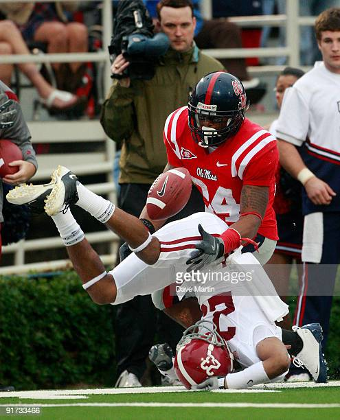 Running back Brandon Bolden of the Mississippi Rebels battles for a pass with Robby Green of the Alabama Crimson Tide during their college football...