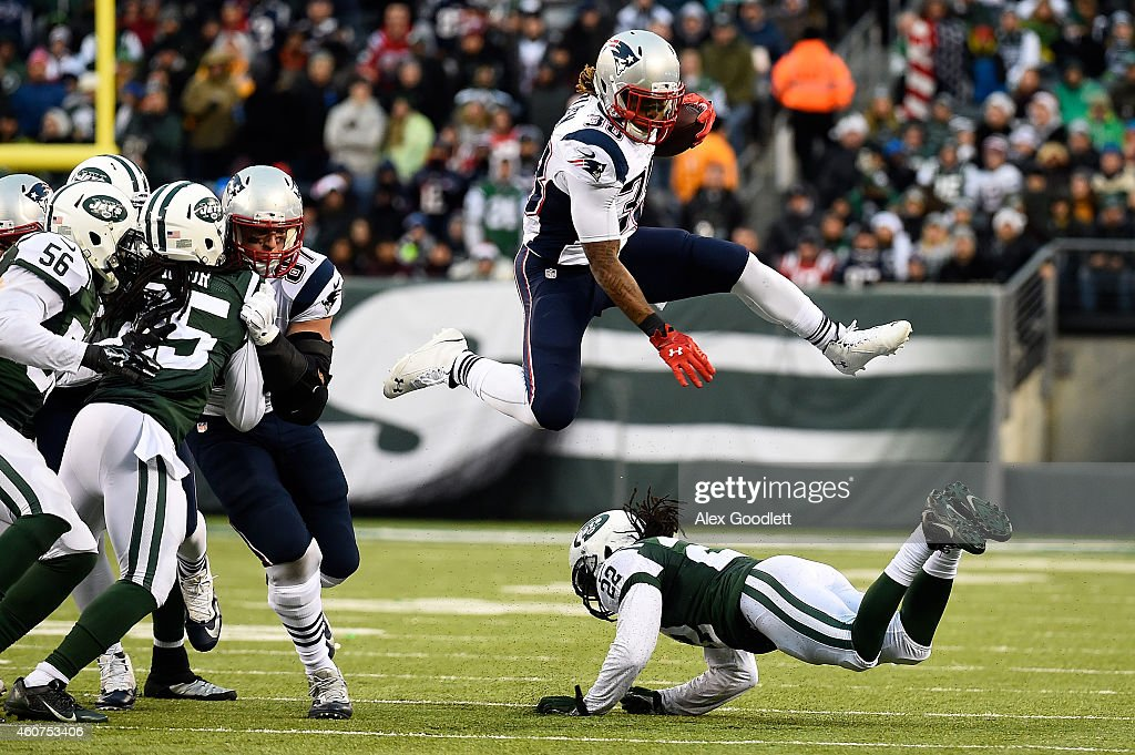 Running back Brandon Bolden #38 of the New England Patriots jumps over cornerback Marcus Williams #22 of the New York Jets in the fourth quarter during a game at MetLife Stadium on December 21, 2014 in East Rutherford, New Jersey.