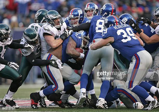 Running back Brandon Jacobs of the New York Giants is stopped by linebacker Stewart Bradley and safety Quintin Mikell of the Philadelphia Eagles...