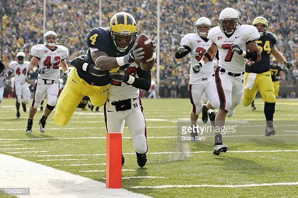 Running back Brandon Minor of the Michigan Wolverines dives for a touchdown as he is hit by defensive back Marcus McClure of the Ball State Cardinals...