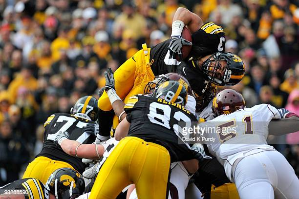 Running back Brandon Wegher of the Iowa Hawkeyes jumps into the end zone for a one yard touchdown as linebacker Gary Tinsley of the Minnesota Golden...