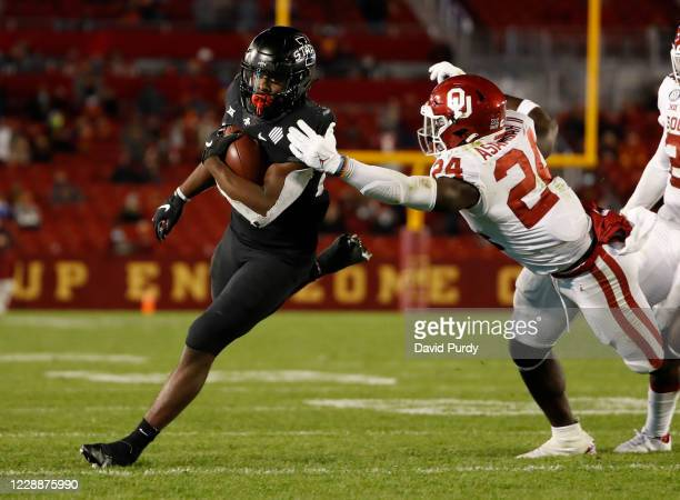 Running back Breece Hall of the Iowa State Cyclones rushes for yards as linebacker Brian Asamoah of the Oklahoma Sooners defends in the first half...