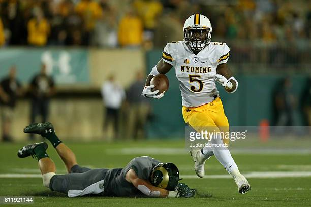 Running back Brian Hill of the Wyoming Cowboys runs for a first down after eluding a tackle by the Colorado State Rams defense at Sonny Lubick Field...