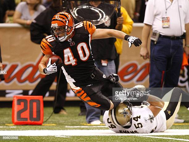 Running back Brian Leonard of the Cincinnati Bengals is tackled by linebacker Troy Evans of the New Orleans Saints during the preseason game on...