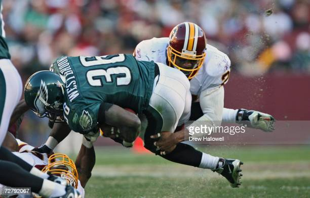 Running back Brian Westbrook of the Philadelphia Eagles gets tackled by safety Sean Taylor of the Washington Redskins at FedEx Field December 10,...