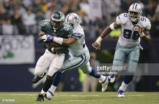 Running back Brian Westbrook of the Philadelphia Eagles tries to break a tackle against the Dallas Cowboys on November 15 2004 at Texas Stadium in...