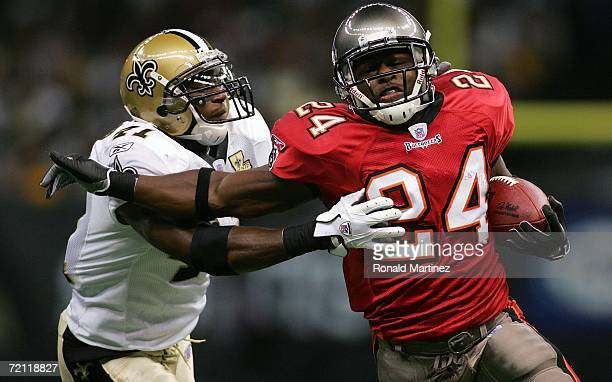 Running back Cadillac Williams of the Tampa Bay Buccaneers runs the ball against Roman Harper of the New Orleans Saints at the Louisiana Superdome on...
