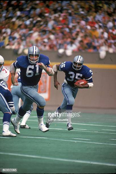 Running back Calvin Hill of the Dallas Cowboys runs behind the block of guard Blaine Nye in a game against the St Louis Cardinals at Busch Stadium on...