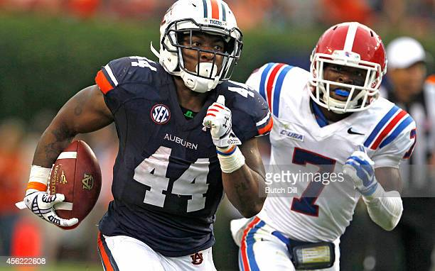Running back Cameron Artis-Payne of the Auburn Tigers gets past defensive back Xavier Woods of the Louisiana Tech Bulldogs as he runs for a first...