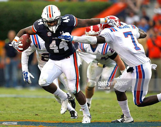 Running back Cameron Artis-Payne of the Auburn Tigers stiff arms defensive back Xavier Woods of the Louisiana Tech Bulldogs as he runs for a first...