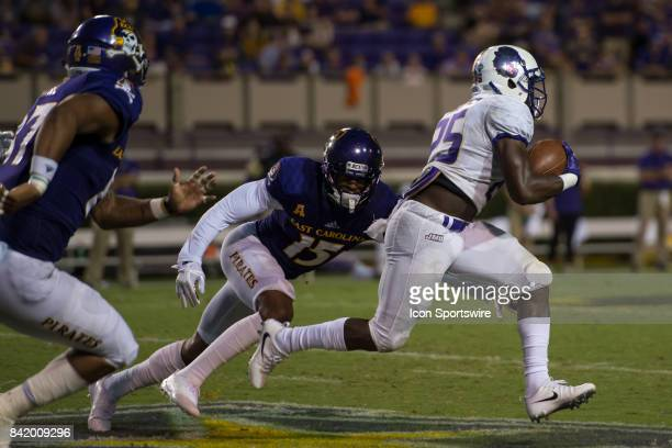 Running back Cardon Johnson of the James Madison Dukes runs out of the tackle of defensive back Korrin Wiggins of the East Carolina Pirates during a...
