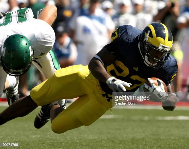 Running back Carlos Brown of the Michigan Wolverines dives for for a touchdown on a nine yard run past safety Ryan Downard of the Eastern Michigan...