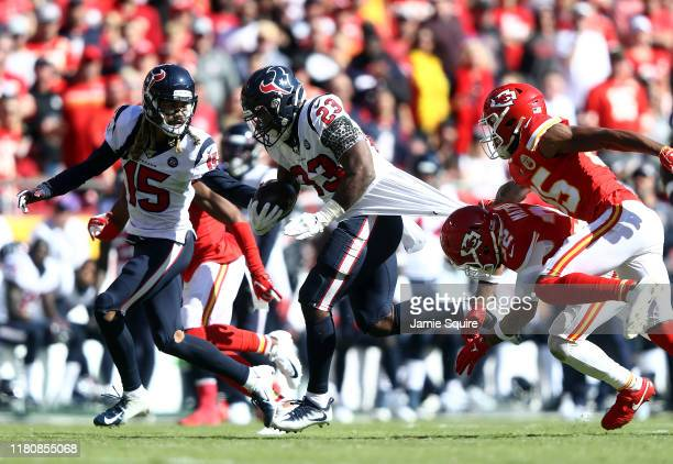 Running back Carlos Hyde of the Houston Texans carries the ball as strong safety Tyrann Mathieu and cornerback Charvarius Ward of the Kansas City...
