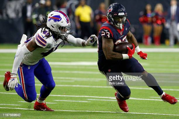 Running back Carlos Hyde of the Houston Texans carries the ball against the Tremaine Edmunds of the Buffalo Bills during the AFC Wild Card Playoff...