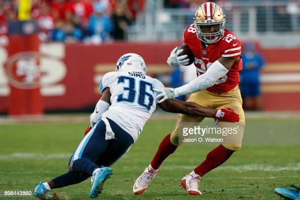 Running back Carlos Hyde of the San Francisco 49ers breaks a tackle from cornerback LeShaun Sims of the Tennessee Titans during the fourth quarter at...