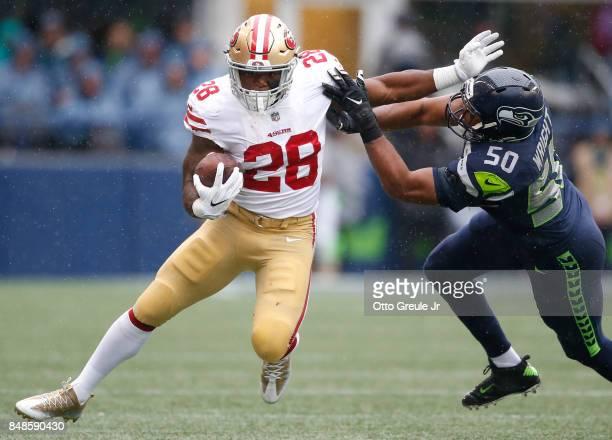 Running back Carlos Hyde of the San Francisco 49ers fends off linebacker KJ Wright of the Seattle Seahawks during the second quarter game at...