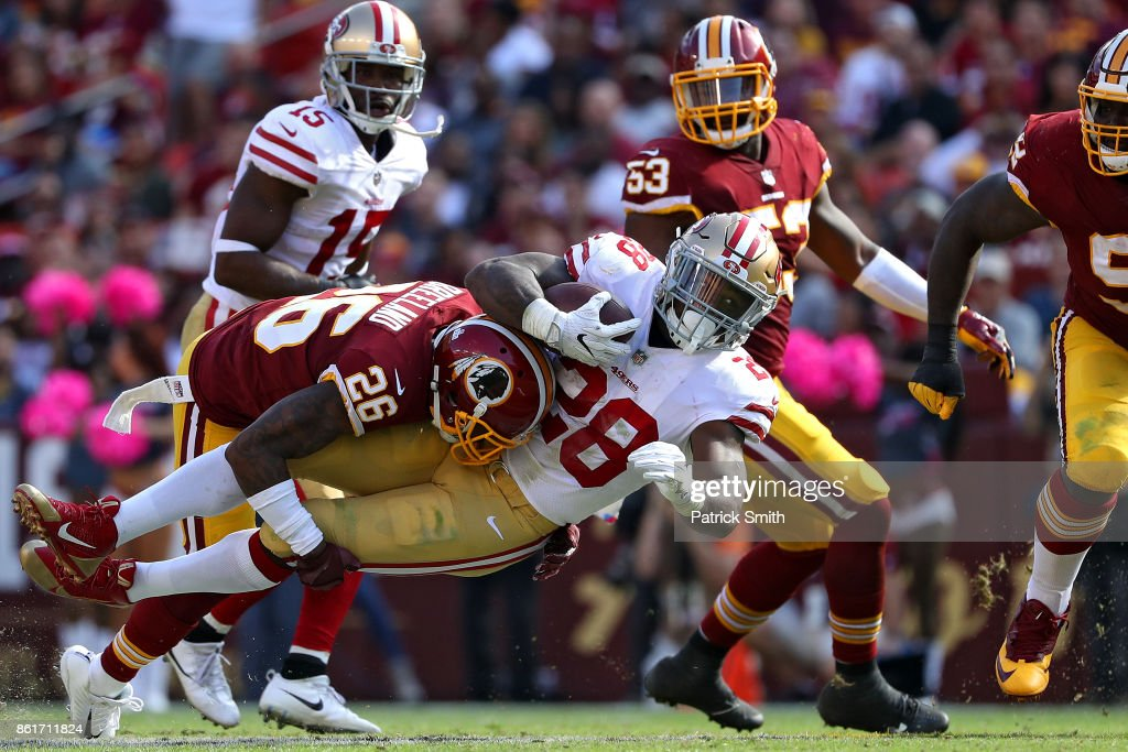 Running back Carlos Hyde #28 of the San Francisco 49ers is tackled by cornerback Bashaud Breeland #26 of the Washington Redskins during the during the third quarter at FedExField on October 15, 2017 in Landover, Maryland.