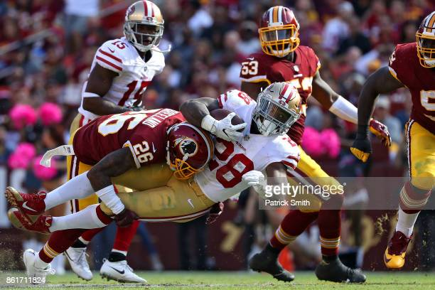 Running back Carlos Hyde of the San Francisco 49ers is tackled by cornerback Bashaud Breeland of the Washington Redskins during the during the third...