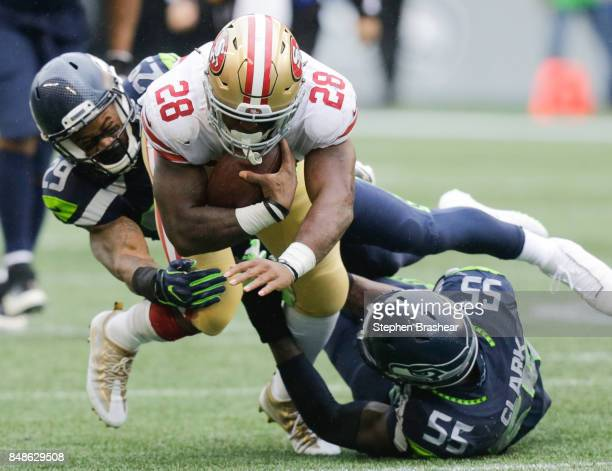 Running back Carlos Hyde of the San Francisco 49ers is taken down by free safety Earl Thomas of the Seattle Seahawks and defensive end Frank Clark...