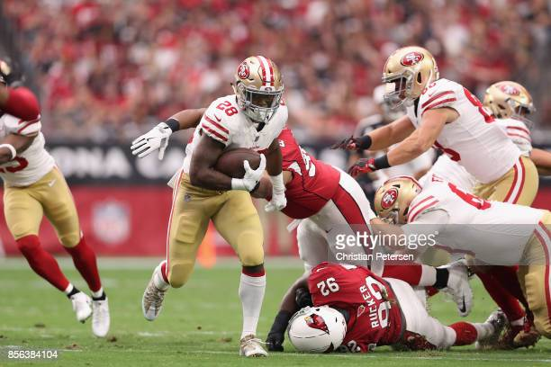 Running back Carlos Hyde of the San Francisco 49ers runs past defensive end Frostee Rucker of the Arizona Cardinals during the first half of the NFL...