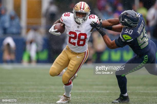 Running back Carlos Hyde of the San Francisco 49ers rushes against linebacker KJ Wright of the Seattle Seahawks at CenturyLink Field on September 17...