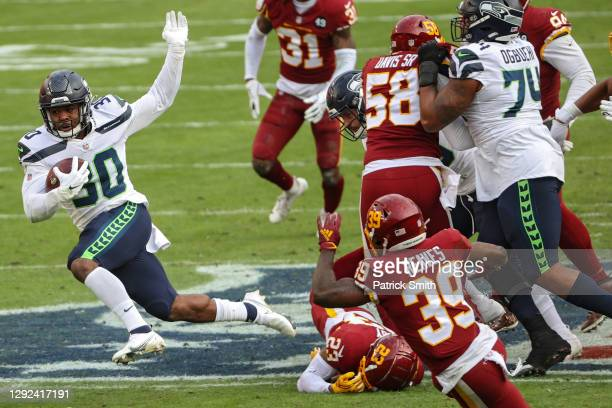 Running back Carlos Hyde of the Seattle Seahawks rushes before scoring a third quarter touchdown against the Washington Football Team at FedExField...