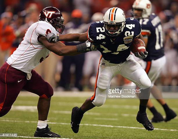 Running back Carnell Williams of the Auburn Tigers stiff arms Vince Hall of the Virginia Tech Hokies during the Nokia Sugar Bowl on January 3 2005 at...